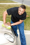 Black man cleaning car. African American man leaning over and cleaning car hood on driveway Stock Photography