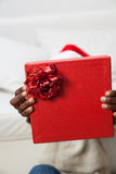 Black man covering his face with gift Stock Photography