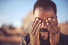 Black man covering his face with his hands Stock Image