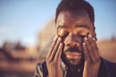 Black man covering his face with his hands Royalty Free Stock Images
