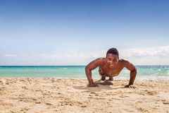 Black man does push up. At the beach Royalty Free Stock Photo