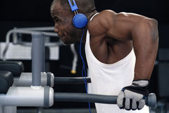 Black man doing exercises dips. Muscular black man in a white t-shirt and blue headphones doing exercises dips Royalty Free Stock Photo
