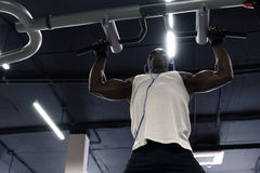 Black man doing exercises pull ups. Black athlete doing pull-up on horizontal bar.Mans fitness at the gym Stock Photography
