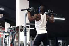 Black man doing exercises pull ups. Back view of a black man wearing white t-shirt doing exercises pull ups Royalty Free Stock Images