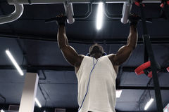 Black man doing exercises pull ups. Front view of a black man wearing white t-shirt doing exercises pull ups Stock Image