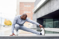 Black man doing stretching before running in urban background Royalty Free Stock Image