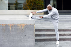 Black man doing stretching before running in urban background Stock Photography