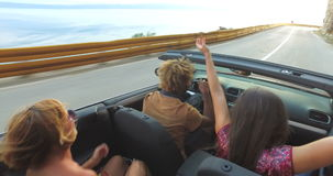 Black man with dreadlocks partying with friends while driving in convertible stock video footage