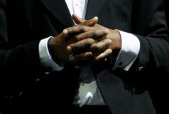 A black man in an elegant suit clasp the hands. Gestures and features of business negotiations royalty free stock photo