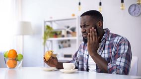 Black man feeling tooth ache from sweet food, eating croissant with coffee. Stock photo royalty free stock photos