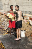 Black man, filled with mud to a European man Stock Photography