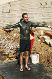 Black man, filled with mud to a European man Stock Photos