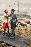 Black man, filled with mud to a European man Stock Images