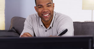 Black man flipping through channels on TV Royalty Free Stock Photos