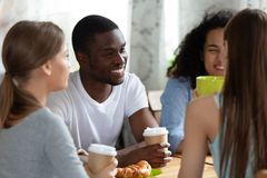 Black man and girls sitting drinking coffe chatting in cafe. Smiling black men sitting at table surrounded by friends diverse girls sitting chatting together stock photo