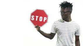 A sad man holds a stop sign and looks the other way. Black man with glasses sadly holding a stop sign stock video