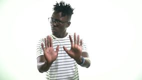 Black man with glasses shows his hands to stop. Man asks to stop showing on white background stock footage