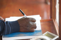 Black man hand with pen. Filling form on table Royalty Free Stock Photography