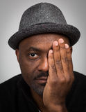Black Man In Hat With Stubble Covering One Eye. A black man wearing a hat with a stubble chin and mustache covering one of his eyes with one hand isolated Stock Photos