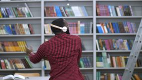 Black man in headphones dancing back to camera. View from the back of african american man making a musical break in library. Handsome male performing expressive