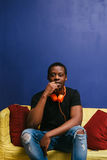 Black man with headphones sit on couch, rest alone Stock Photos
