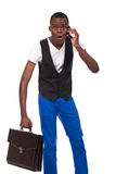 Black man holding briefcase and talks on the phone Royalty Free Stock Image