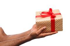 Black man holding gift box isolated on white background. Black man holding a gift box with red ribbon in hands isolated on white background. Present, holiday Royalty Free Stock Image