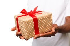 Black man holding gift box isolated on white background. Black man holding a gift box with red ribbon in hands isolated on white background. Present, holiday Royalty Free Stock Images