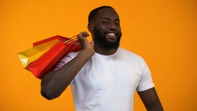 Black man holding shopping bags and showing thumbs up sign, season discount. Stock footage stock video