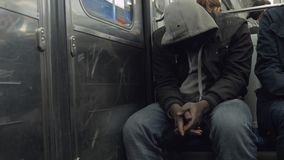 Black man in the hood in subway train. PARIS, FRANCE - SEPTEMBER 29, 2017: Black man traveling in subway train. He sitting with head down and hiding his face stock video