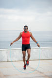 Black man jumping rope. Cheerful male runner jumping rope for warming up. Black athlete training and doing cardio exercise outside Stock Photos