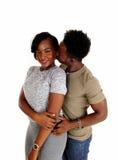Black man kissing girlfriend. Royalty Free Stock Image