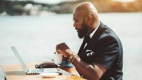 Black man with laptop in street bar royalty free stock photography
