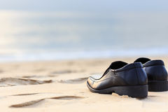 Black man leather shoe on the beach. Close up black man leather shoe on the beach Stock Photos