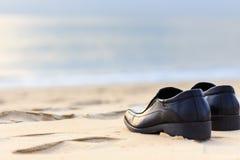 Black man leather shoe on the beach Stock Photos