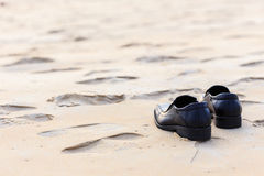 Black man leather shoe on the beach Royalty Free Stock Images