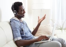 Black man listening music. African American man listening music with headphones and laptop Stock Images