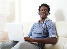 Black man listening music. African American man listening music with headphones and laptop Royalty Free Stock Image