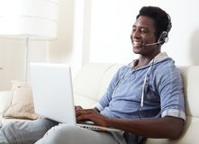 Black man listening music. African American man listening music with headphones and laptop Royalty Free Stock Photography