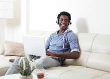 Black man listening music. African American man listening music with headphones and laptop Royalty Free Stock Images