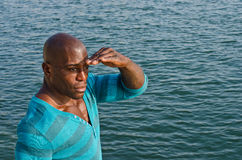 Black man looking far away on the sea. Royalty Free Stock Photography