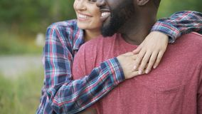 Black man and mixed race woman tenderly hugging, happy people smiling together