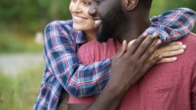 Black man and mixed race woman tenderly hugging, happy people smiling together stock photo