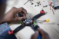Black man mounting and soldering racing drone on wooden table stock images