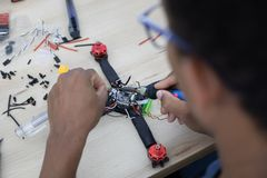 Black man mounting and soldering racing drone on wooden table. With copy space stock image