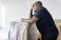 Black man moving heavy furniture home renovation concept Royalty Free Stock Image