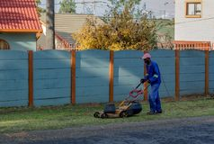 Black man mowing a lawn at a private residence royalty free stock photography