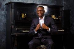 Black man near the piano. Black man poses near the piano royalty free stock image
