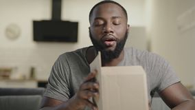 Black man opening box sitting on couch. Surprised male person opening box. stock footage