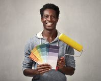 Black man with painting roller. Young african american man with painting roller. House renovation Stock Photography